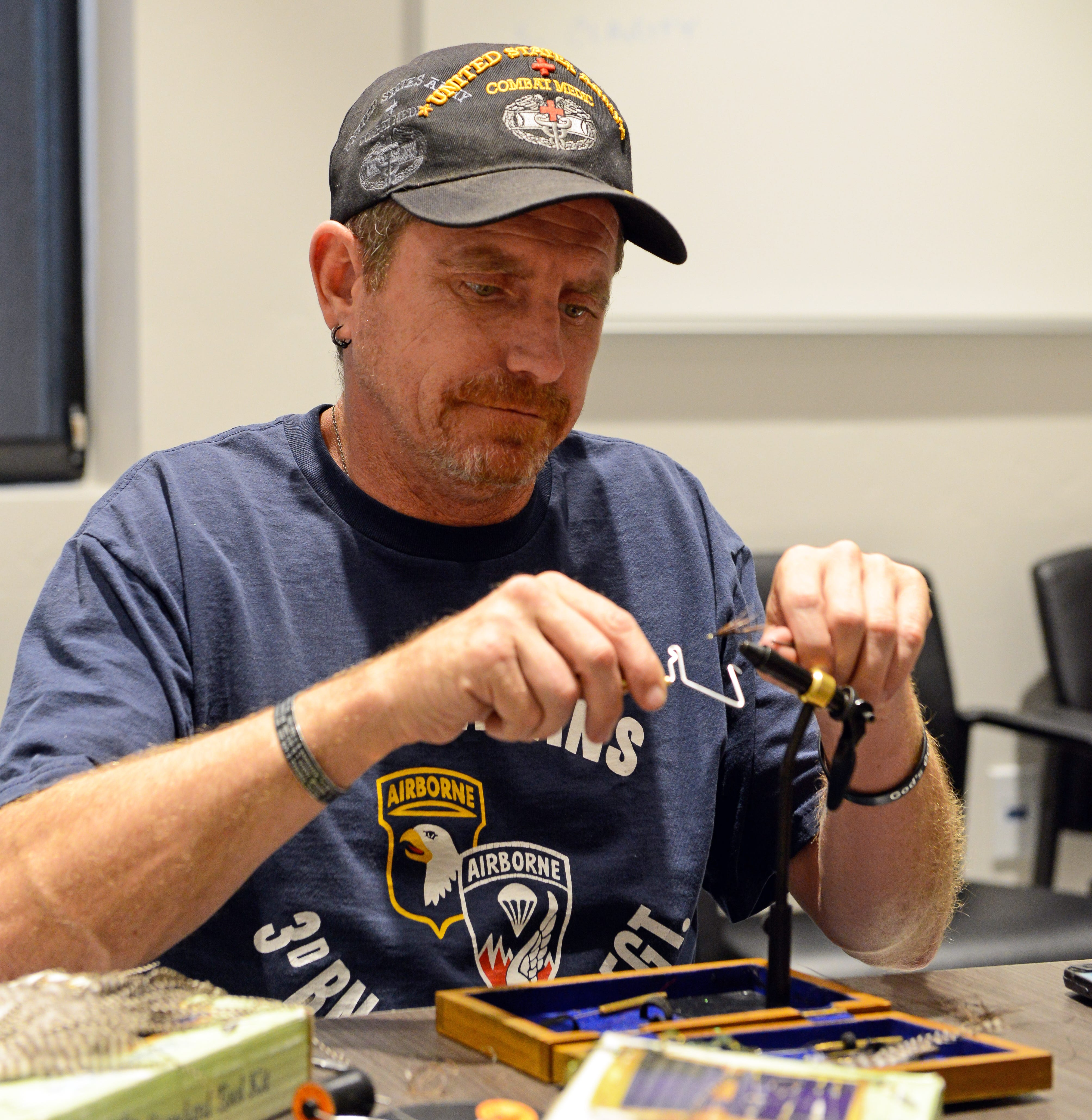 "Ray Kirby ties a fishing fly during a ""Fly Time"" event hosted by Project Healing Waters, a group that helps disabled veterans recover through the ""therapeutic benefits of fly fishing."""
