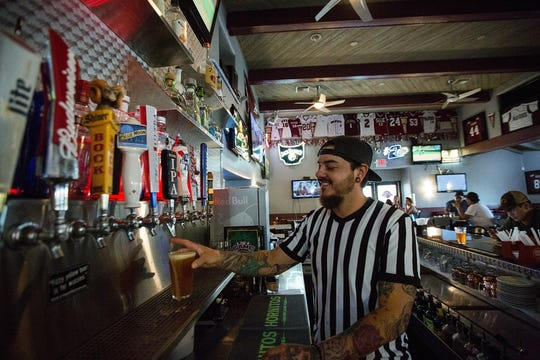 Daniel Castaneda, a bartender at The Game Sports Bar and Grill on Solano Drive, pours a beer in the restaurant's bar, where New Mexico State University memorabilia hangs.