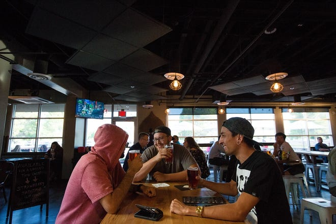 Domenic Altamirano, right, Dallin Baker, center, and Alex Monroy, drink a few beers at Bosque Brewing Company Public House on University Avenue on Tuesday, Aug. 14.