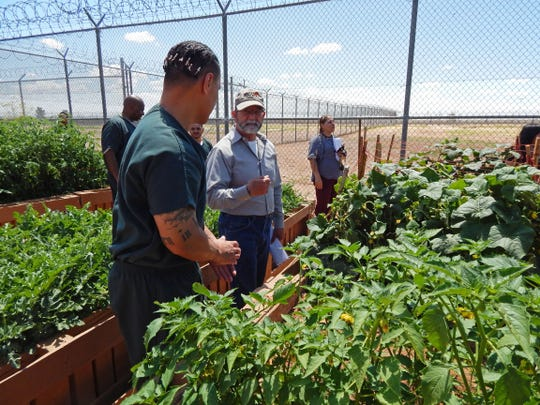 New Mexico State University Cooperative Extension Service agent Jeff Anderson, right, speaks with an inmate at the Southern New Mexico Correctional Facility. Anderson assisted inmates at the prison in establishing a therapeutic garden program in 2016.