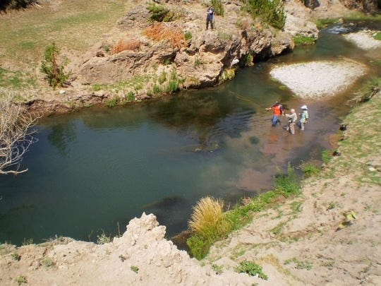 Volunteers from Project Healing Waters help disabled veterans fish on the Rio Peñasco in Mayhill, New Mexico.