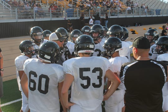 The squad huddles for some offensive coaching during the scrimmage on Thursday.