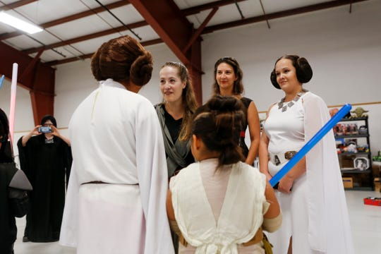 From left, Contest judges Heather Gallion, Sarah Alcon, Kahlan Thompson and Rebekah Garcia talk to contestants Alyssa Etcitty, bottom left, and April Hunt Thursday during a Star Wars themed costume contest during the San Juan County Fair at McGee Park Convention Center in Farmington.