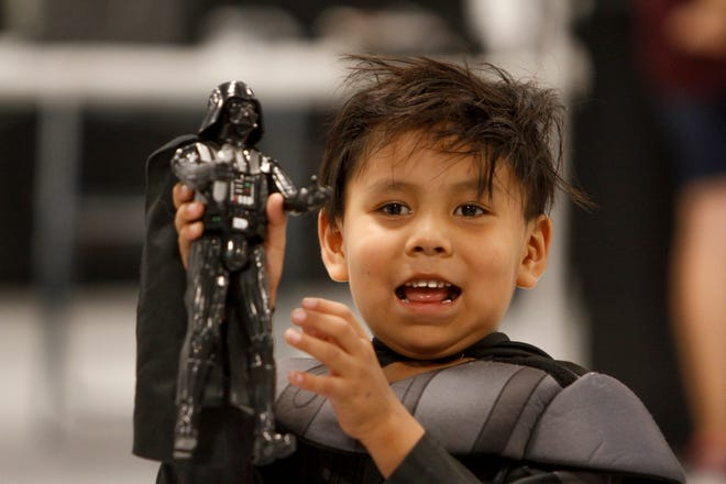 Clayton Blatchford shows his first place award to his uncle Frank Blatchford Thursdayduring a Star Wars themed costume contest during the San Juan County Fair at McGee Park Convention Center in Farmington.