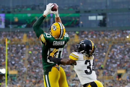 Green Bay Packers tight end Jimmy Graham (80) catches a touchdown pass as Pittsburgh Steelers defensive back Terrell Edmunds (34) defends in the first quarter of an NFL preseason game at Lambeau Field on Thursday, August 16, 2018 in Green Bay, Wis.