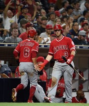 David Fletcher #6 of the Los Angeles Angels is congratulated by Taylor Ward after scoring during the sixth inning of a baseball game against the San Diego Padres at PETCO Park on August 15, 2018 in San Diego, California. (Photo by Denis Poroy/Getty Images)