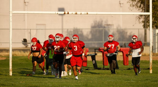 Players head in for water during practice at Mesa Community College in Mesa, Ariz. on Aug. 16, 2018.