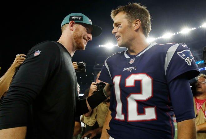 New England Patriots quarterback Tom Brady (12) meets Philadelphia Eagles quarterback Carson Wentz (11) after a preseason game at Gillette Stadium. The Patriots defeated the Eagles, 37-20.
