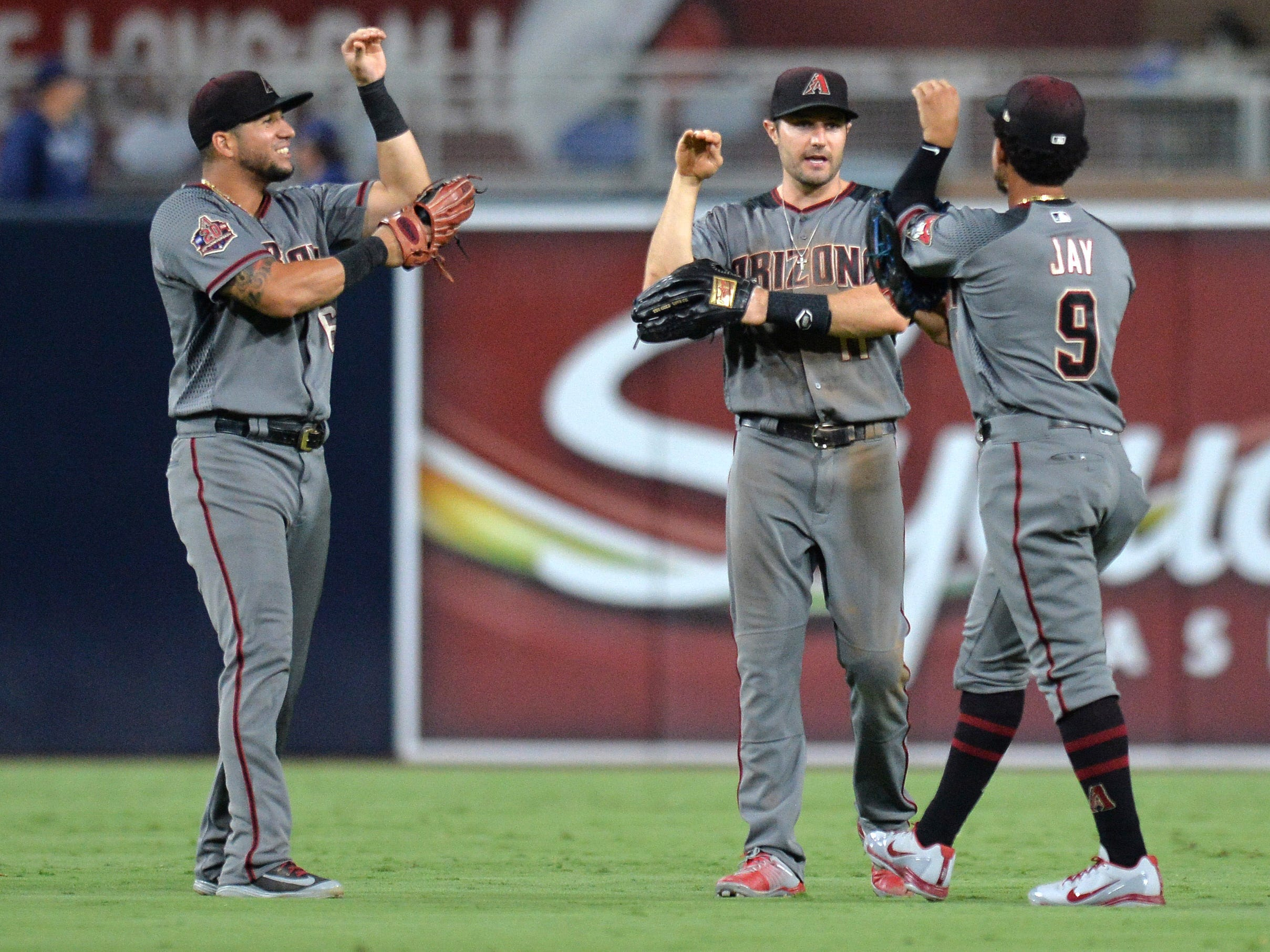 Aug 16, 2018; San Diego, CA, USA; Arizona Diamondbacks left fielder David Peralta (left) center fielder A.J. Pollock (center) and right fielder Jon Jay (9) celebrate a 5-1 win over the San Diego Padres at Petco Park.