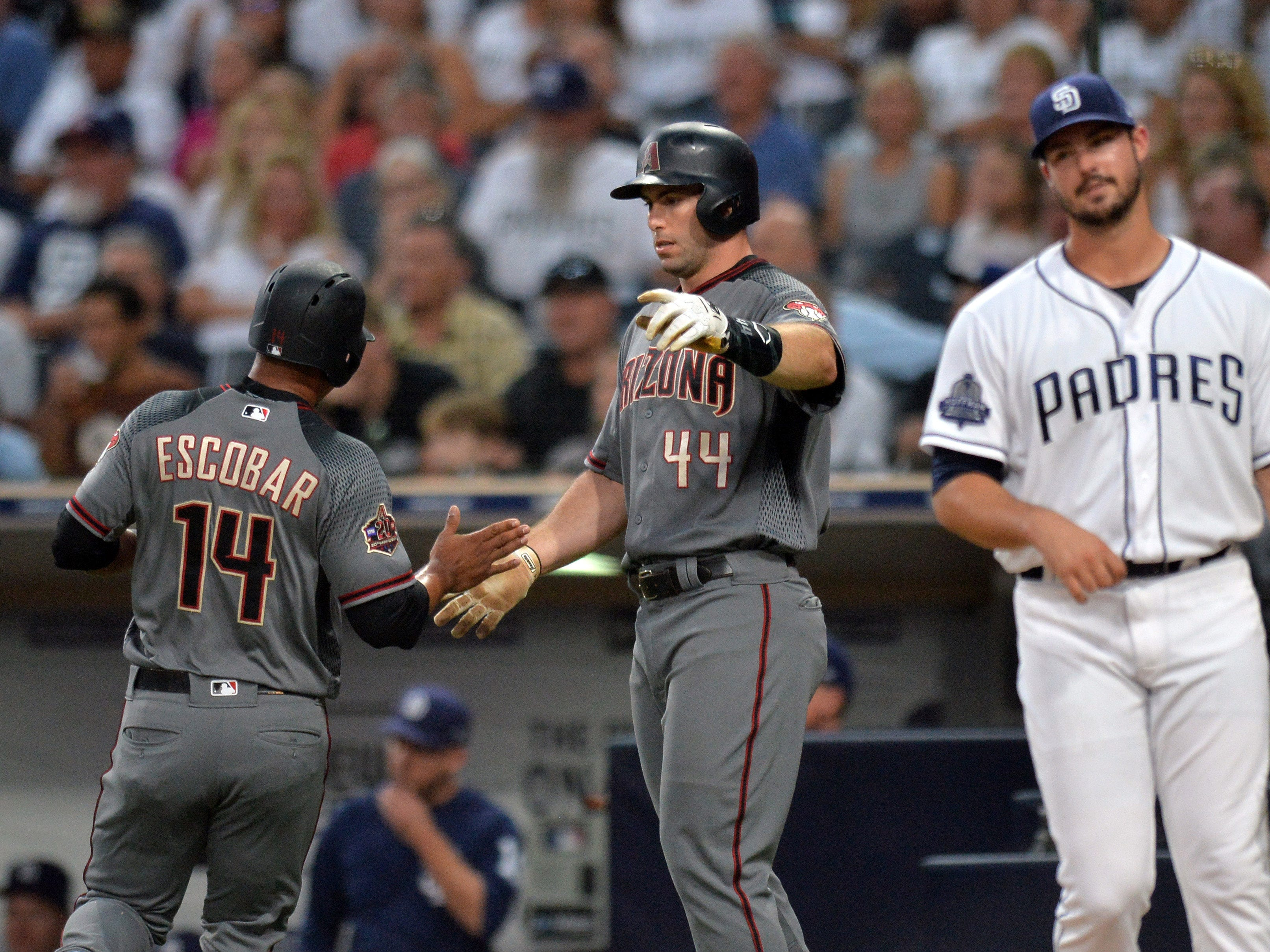Aug 16, 2018; San Diego, CA, USA; Arizona Diamondbacks first baseman Paul Goldschmidt (44) and third baseman Eduardo Escobar (14) celebrate after scoring on a single by catcher Alex Avila (not pictured) during the first inning as San Diego Padres starting pitcher Jacob Nix (right) reacts at Petco Park.