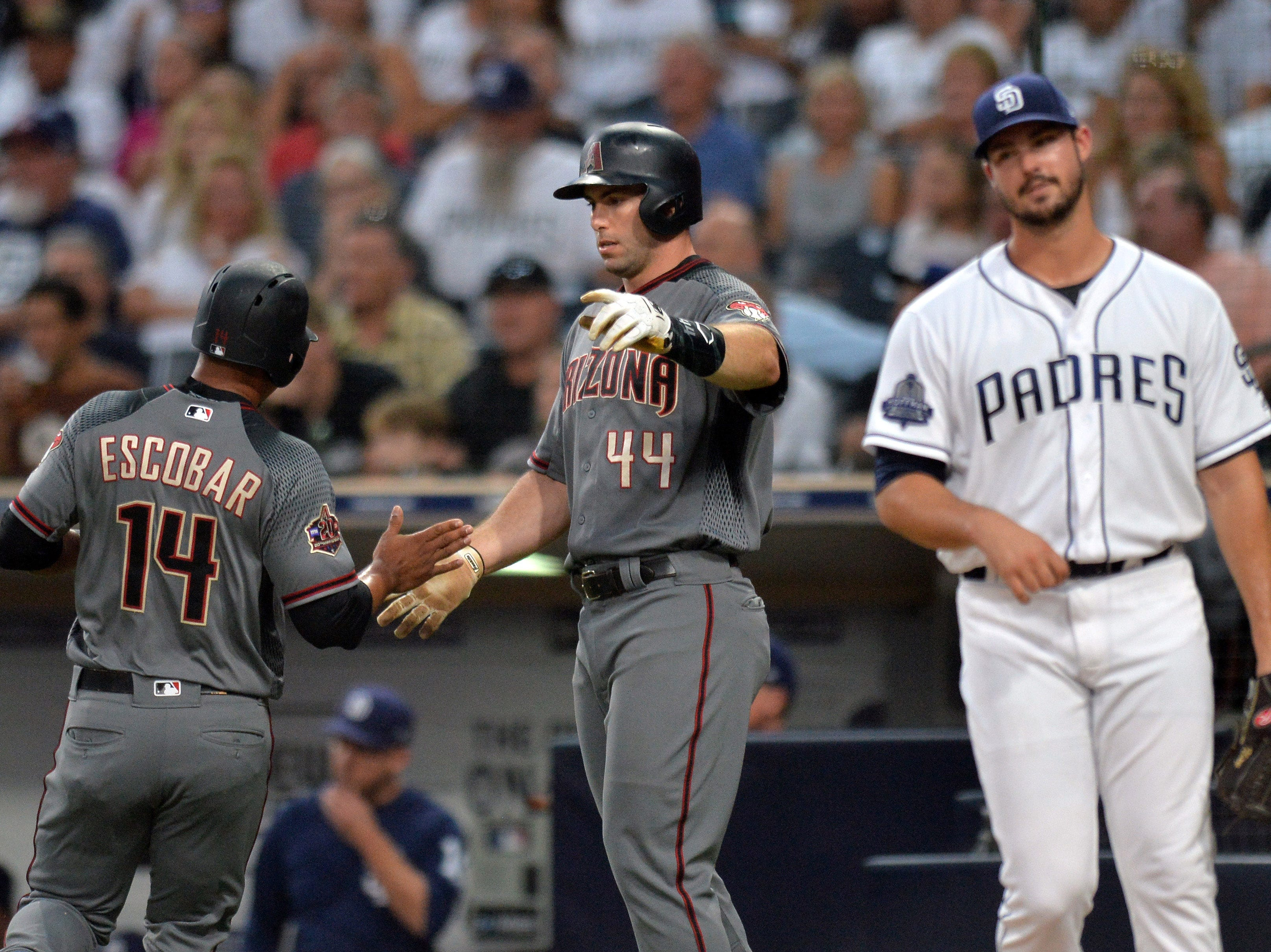 Aug 16, 2018; San Diego, CA, USA; Arizona Diamondbacks first baseman Paul Goldschmidt (44) and third baseman Eduardo Escobar (14) celebrate after scoring on a single by catcher Alex Avila (not pictured) during the first inning as San Diego Padres starting pitcher Jacob Nix (right) reacts at Petco Park. Mandatory Credit: Jake Roth-USA TODAY Sports