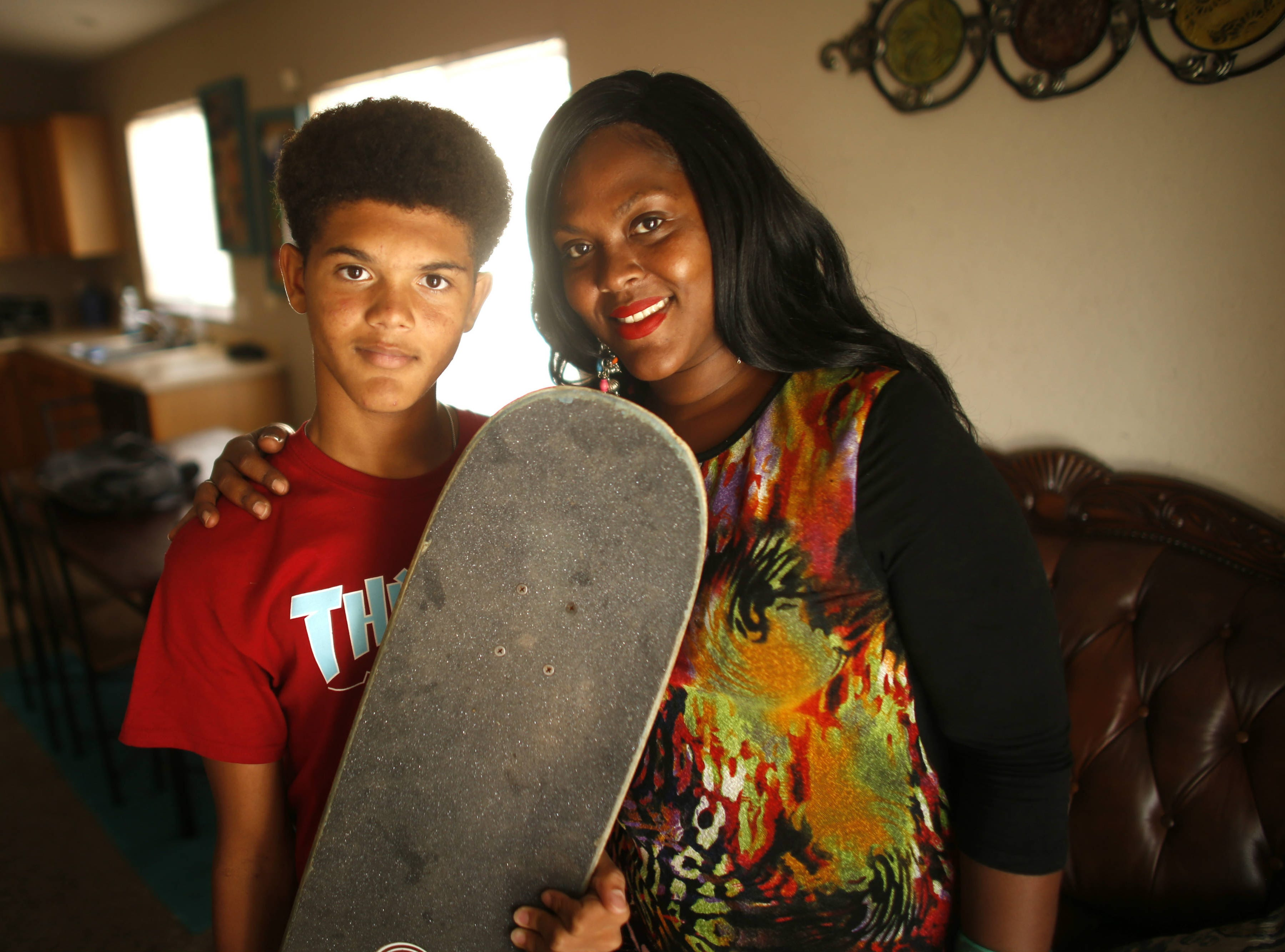 Krista Wiedman puts an arm around her son, Josiah, as he holds his skateboard, which they believe helped protect him from the full force of the lightning, at their home in El Mirage on Aug. 16, 2018.