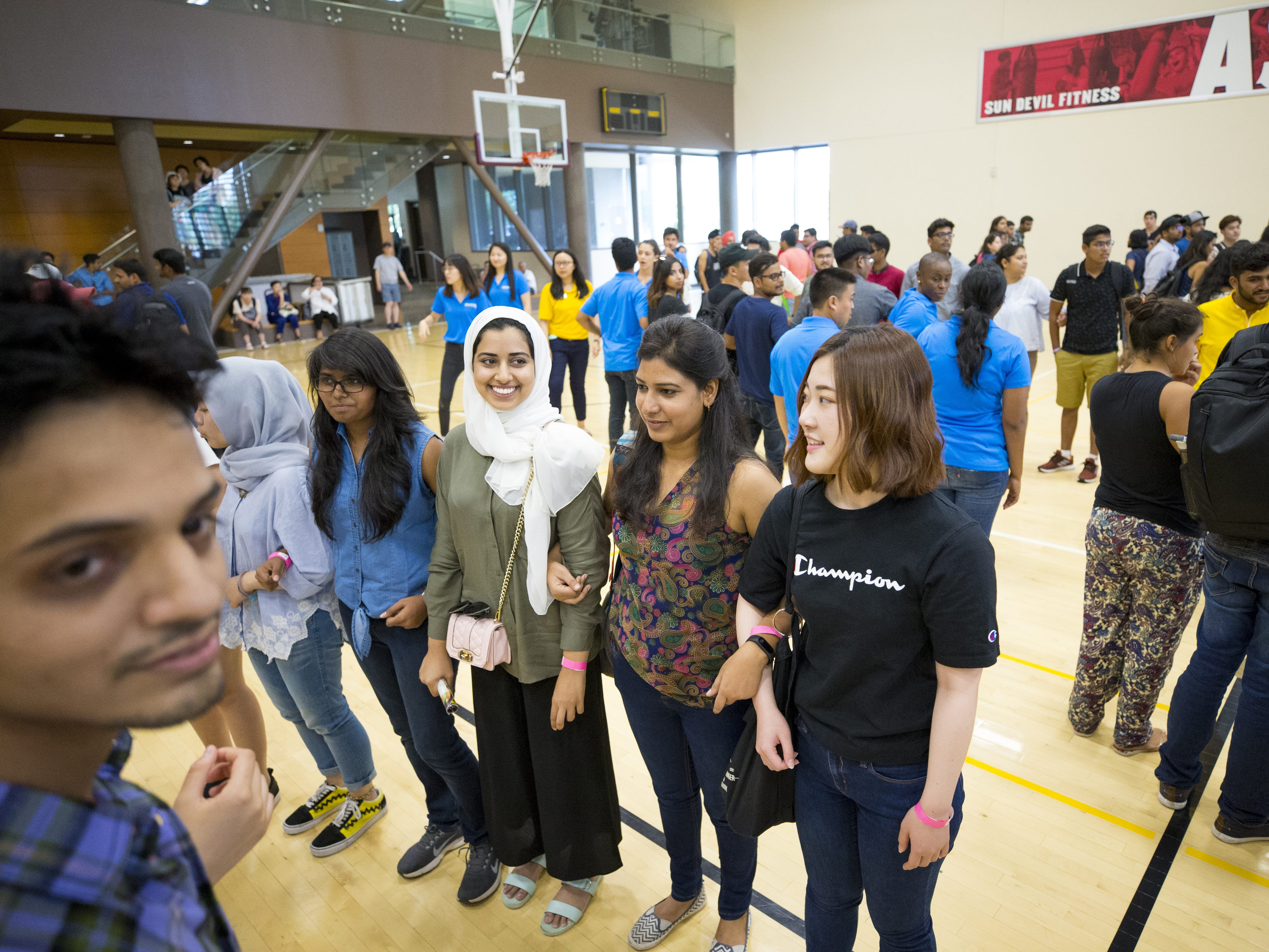ASU international students Dania Alarfaj, from Saudi Arabia, Bhawana Prasad, from India, and Natsuki Kanno, from Japan, participate in Play Fair at the Sun Devil Fitness Center in Tempe during their orientation on Aug. 8, 2018.