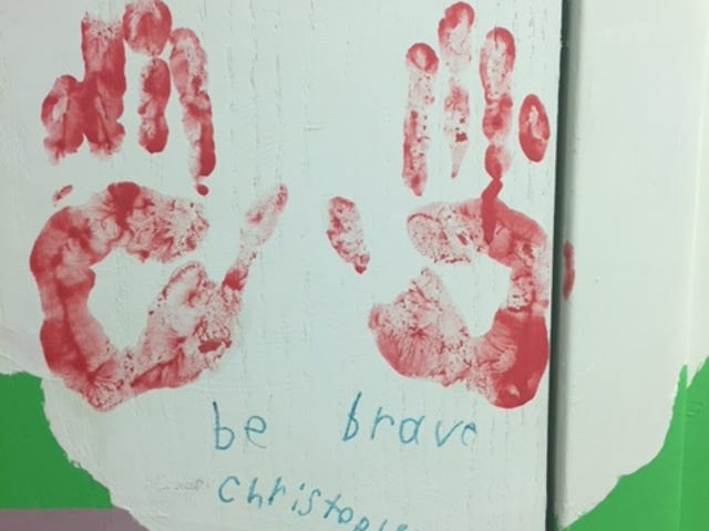 A mural of healing in the SARCC office in downtown Lebanon spans several years of handprints and messages from survivors, including this one from Christopher: be brave.