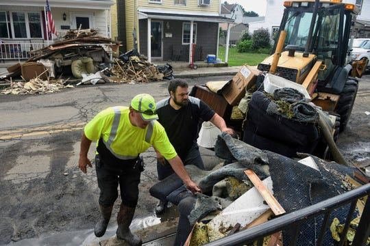 Jim Scheibley, road supervisor for Tremont Borough, left, and Matt Wolfgang, of Donaldson, Pa., right, fill a front end loader with flood damaged items from homes in Tremont, Pa., Tuesday, Aug. 14, 2018. Heavy rains on Monday triggered flash flooding in parts of central and eastern Pennsylvania, closing down a heavily traveled interstate and sending water into homes in the mountainous coal regions. (Jacqueline Dormer/Republican-Herald via AP)
