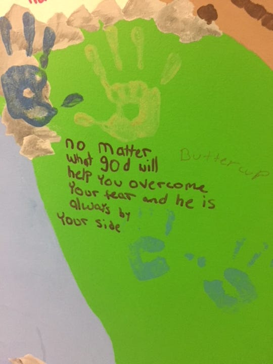 A message of faith is written near the handprints of a child survivor of sexual assault on the healing mural in the Lebanon office of SARCC of Lebanon County.