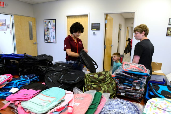 The Salvation Army director Maureen Saponari helps Brandon Fenton, who will be in the ninth grade at Port Clinton, find a large backpack.