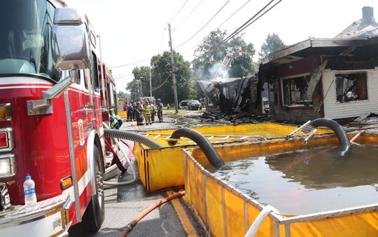 Firefighters from several New York and Connecticut fire departments assist Dover firefighters in battling a blaze that destroyed a building on Route 22 in Dover on Friday. Water had to be shuttled into the scene by tanker trucks.