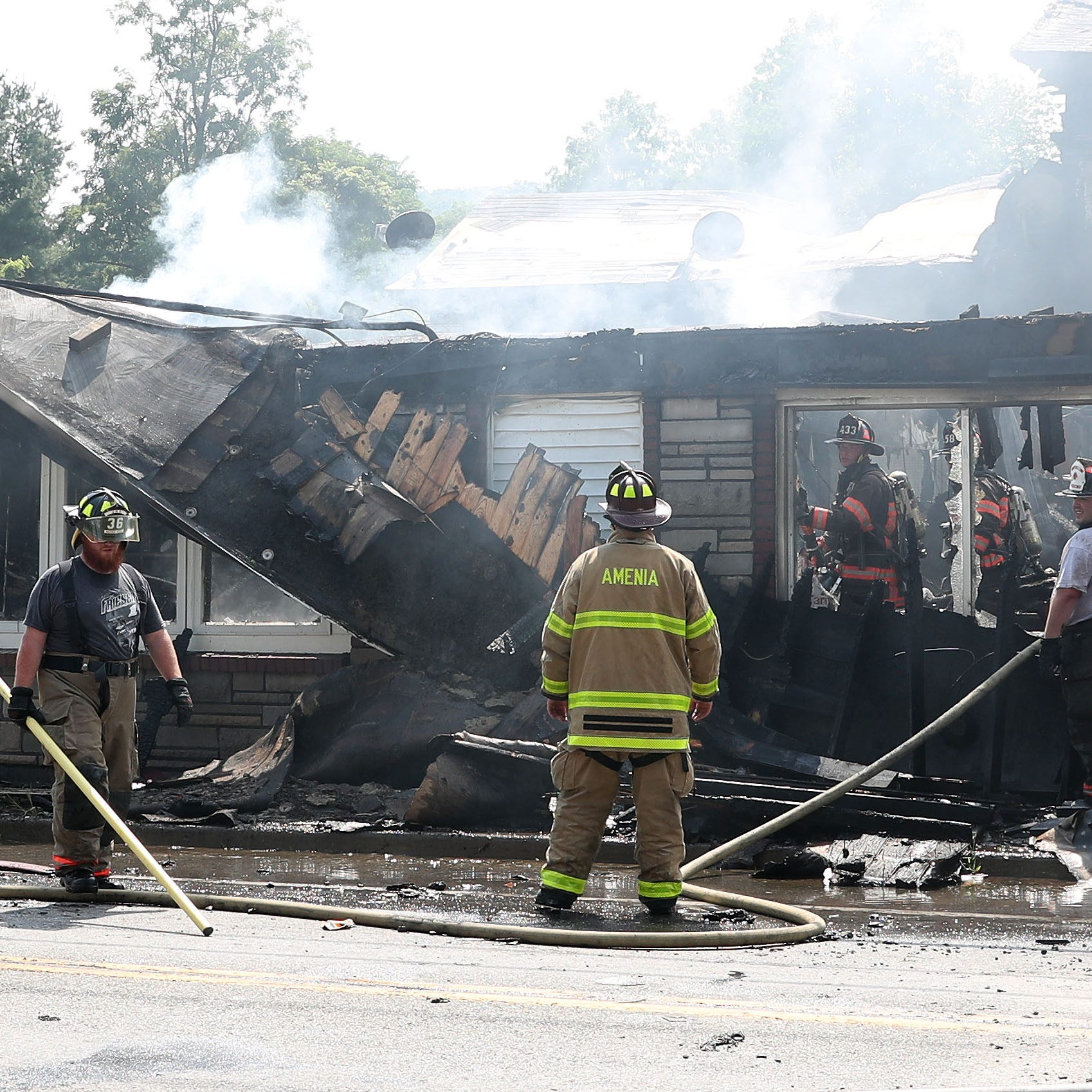 Firefighters from New York and Connecticut fire departments assist Dover firefighters in battling a fire that destroyed a building on Route 22 in Dover on Friday. The fire caused Route 22 to be shut in both directions.