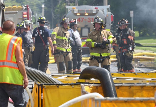 Firefighters from several New York and Connecticut fire departments assist Dover firefighters in battling a blaze that destroyed a building on Route 22 in Dover on Friday.