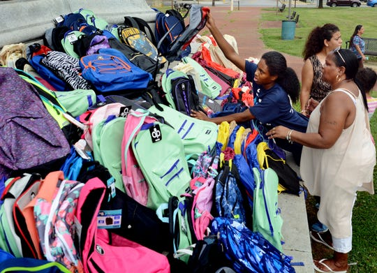Crispus Attucks Summer Career Employment Academy student Armani Givens, 14, places book bags with volunteer Karen Washington during the York City United Back to School Resource Fair at Penn Park Friday, August 17, 2018. The fair is designed to supply school supplies to students for the upcoming year. About 1000 book bags were scheduled to be provided during the event. Bill Kalina photo