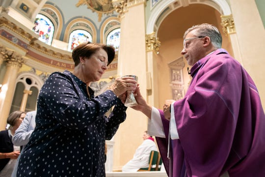 A parishioner takes the chalice from a priest during communion at 'Mass of Forgiveness' at Saint Patrick Cathedral in Harrisburg on Friday, August 17, 2018. The mass was part the Church's 'on-going need for repentance and healing,' according to the Diocese of Harrisburg's website.