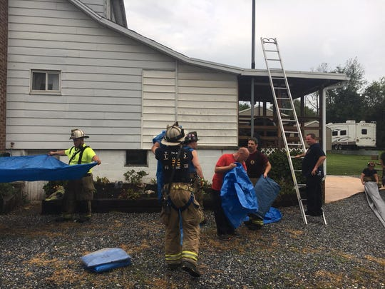Firefighters pack up extra tarp after using tarp and plastic to temporarily patch the roof of a house along Copenhaffer Road in Conewago Township. The roof blew off during Friday evening's storm, landing in a field behind the garage.