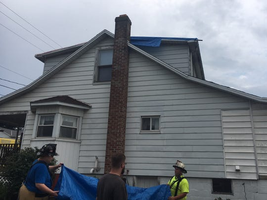 A look up at the roof of a house along Copenhaffer Road in Conewago Township. The metal roof blew off in Friday evening's storm, and firefighters patched the opening with tarp and plastic.