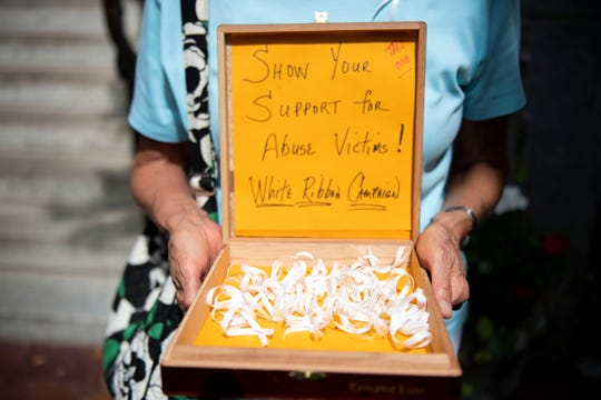 Irene Youngman, of Hershey, holds a box of white ribbons that parishioners could wear to support the survivors of clergy abuse, outside of Saint Patrick Cathedral prior to the 'Mass of Forgiveness'  in Harrisburg on Friday, August 17, 2018. The mass was part the Church's 'on-going need for repentance and healing,' according to the Diocese of Harrisburg's website.