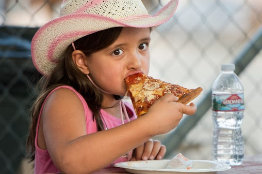 Harley Lassey, 6, from Yerington, enjoys a pizza at the fair.