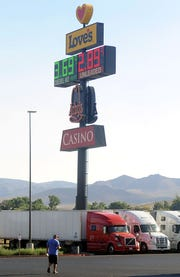 A trucker walks to his rig, parked at a truck stop in Fernley.