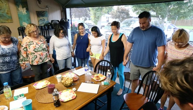 After people have shared their stories of loved ones who died from addiction, members of the Forever in Our Hearts, Walking Together grief support group recite the Serenity Prayer.