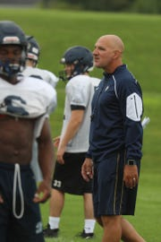 Victor High football coach Geoff Mandile looks over as players start to get in position during practice.