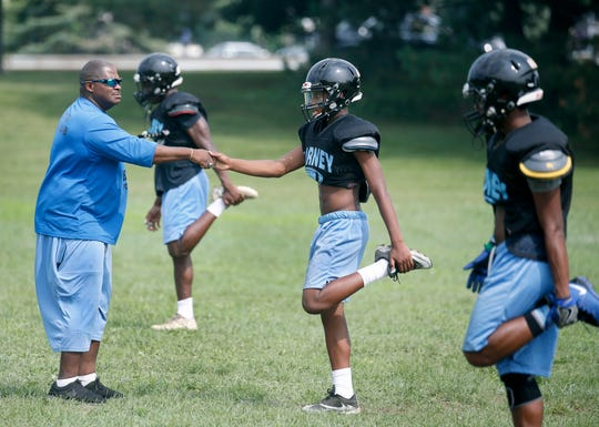 Bishop Kearney head coach Rick Gause shakes hands with Shariek Thompson during football practice.