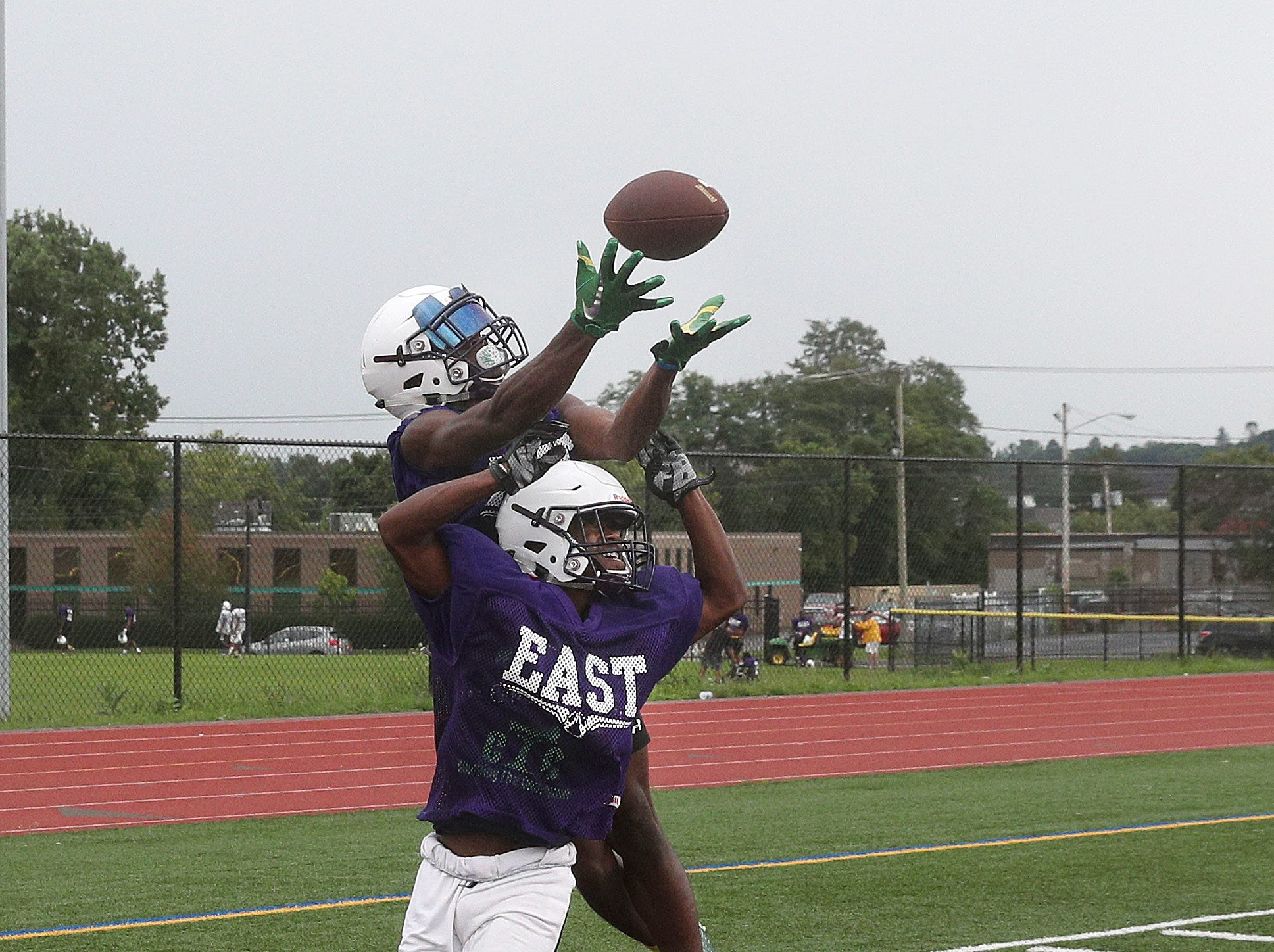 East's Seven McGee goes over Malik McCray to catch a pass in the corner of the end zone during one-on-one drills during  practice.