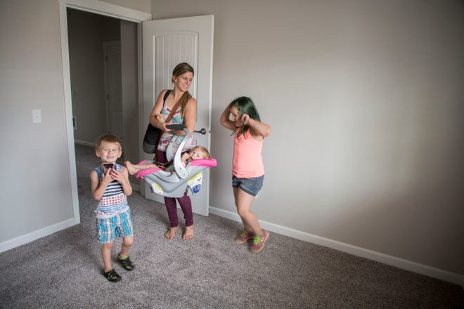 Susan Qualey, center, holds her youngest daughter, Brooklyn Qualey, 1, and watches as her youngest son, Ryder Qualey, 4, and oldest daughter Savannah Qualey, 8, get excited over the bedrooms in their new apartment at Cornerstone Apartments in Salem, Oregon, Thursday August 16, 2018. Thursday August 16, 2018. The complex is the first in a set of Local Innovation and Fast Track homes to open after Oregon lawmakers approved $40 million in awards toward the program in 2015.