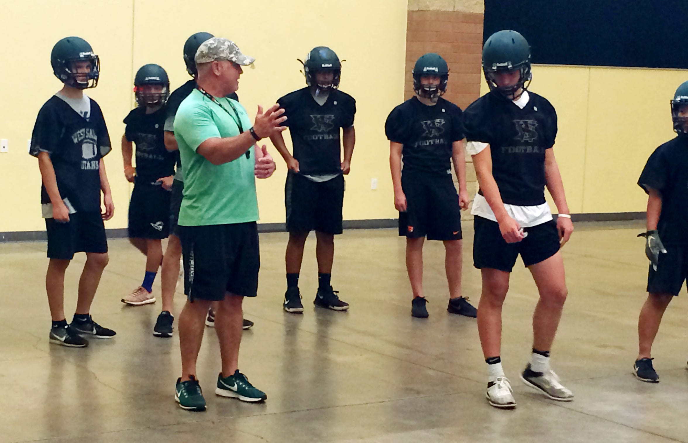 West Salem football coach Shawn Stanley works with players during an indoor drill Tuesday, Aug. 14, 2018. The team practiced indoors because of concerns over the air quality.