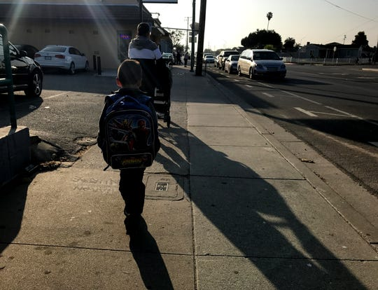 A parent and child walk to school in East Salinas on Thursday.