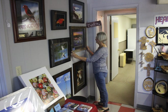 Out of the Box owner Jan Mullins adjusts a painting at the store at 15 North Tyler St.