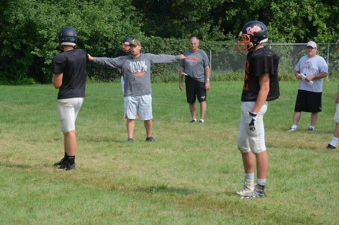 Coach Jordan Huska (center) works with the Dell Rapids High School football team at a recent practice.