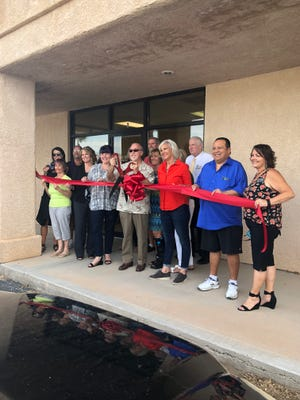Mayor Al Litman, joined by owners Mary Bundy and Susan Forsyth, cuts the ribbon at the ribbon cutting ceremony for new Mesquite business, Bridge Insurance.