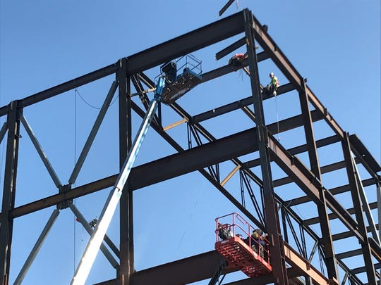 Construction crews weld steel beams onto the frame of the new Human Performance Center at Dixie State University on Monday, Aug. 13, 2018.