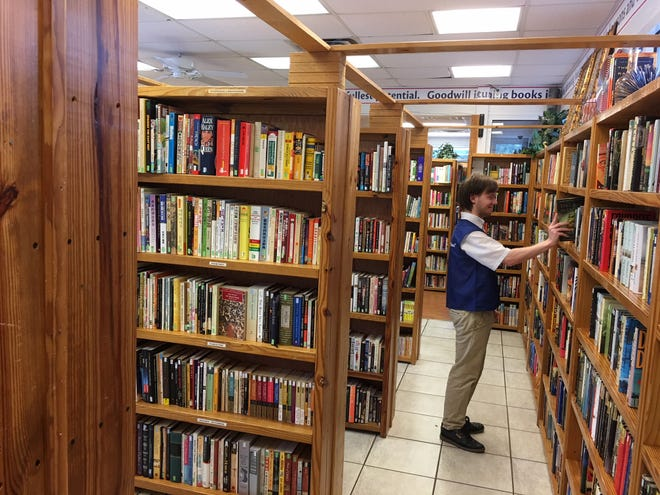 Ethan Wright stacks books at the Thomasville Road Goodwill bookstore.