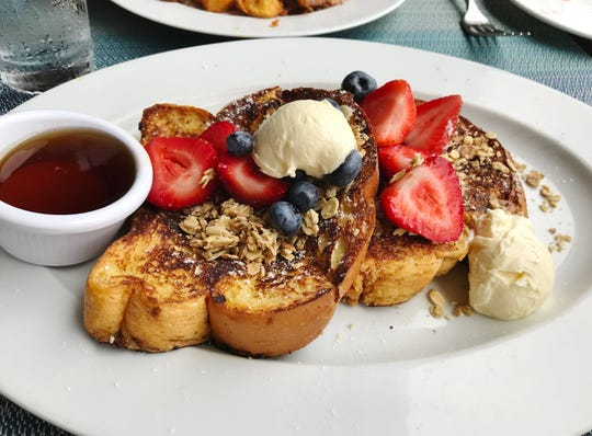 Kyle G's Prime Seafood's granola French toast was part of the restaurant's Sunday brunch. Thick slices of bread were dipped in batter, topped with granola, and griddled. It was served with fresh berries, a large scoop of mascarpone butter and, best of all, real maple syrup.