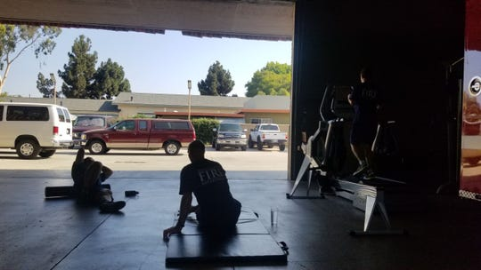From left, Ventura firefighter Brandon Bencomo, Capt. Thomas Hoffman and engineer Jan Hargett work out at Ventura Fire Station No. 1.