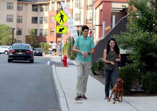 Thomas Re and his wife Nicole Addonizio walk their ten-month old puppy Luna during a walk through Rivertowns Square, a mixed-use development in Dobbs Ferry Aug. 16, 2018. The couple live in the Danforth Apartments, a luxury rental building located in the development. The development includes restaurants, a gym, a hotel, a movie theater, and the apartment building.