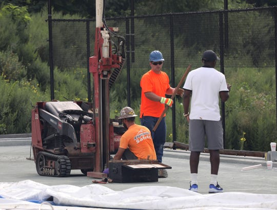 Kela Simunyola, right, operator of Kela Tennis at the Mount Vernon Tennis Center, watches as workers prepare to remove soil from under the tennis court surface, Aug. 17, 2018.