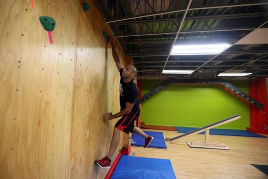 Noel Reyes, Ninja trainer at Westchester Gym in Elmsford, tries out the rock wall obstacle in the new Ninja Warrior Room at the gym Aug. 17, 2018. Many of the obstacles in the room are replicas of the obstacles contestants on the American Ninja Warrior television show must successfully complete. Reyes has been a contestant on the show multiple times.