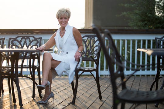 Lori Weldon wears a long ecru sleeveless vest over an ecru skirt with front slits and beaded V-neck sleeveless top, all from White House Black Market, with a pair of taupe beaded and pearl heels from INC International Concepts.
