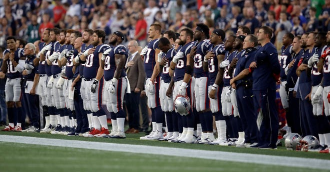 New England Patriots players stand for the national anthem before a preseason NFL football game against the Philadelphia Eagles, Thursday, Aug. 16, 2018, in Foxborough, Mass. (AP Photo/Charles Krupa)